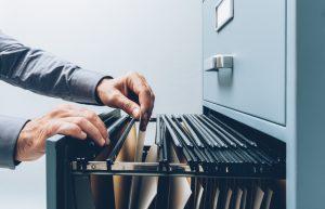 man rifling through a file cabinet