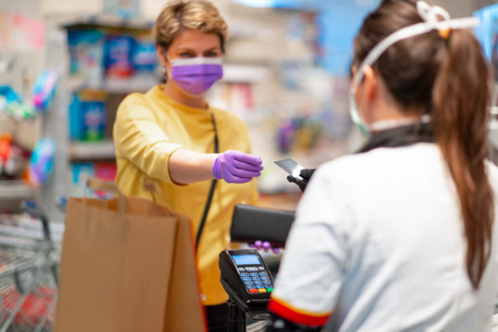 Woman with wallet wearing protective face mask and gloves to prevent viruses taking credit card back from cashier at cash register