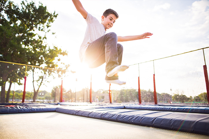 kid jumping on a trampoline