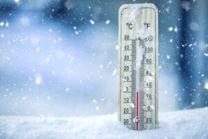 thermometer in snow showing a temperature of zero